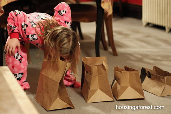 Bite Me as a 15 Minute to Win It Party Game. The challenge was to pick up 5 paper bags cut at varying heights using only our mouths and place them on a table. Make sure that your knees or hands don't touch the floor! That is what makes this game so difficult.