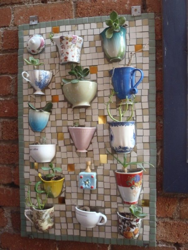 Teacups mosaic board. It allows plants to extend upward rather than grow along the surface of the garden. Doesn't take a lot of space and look so beautiful at the same time.