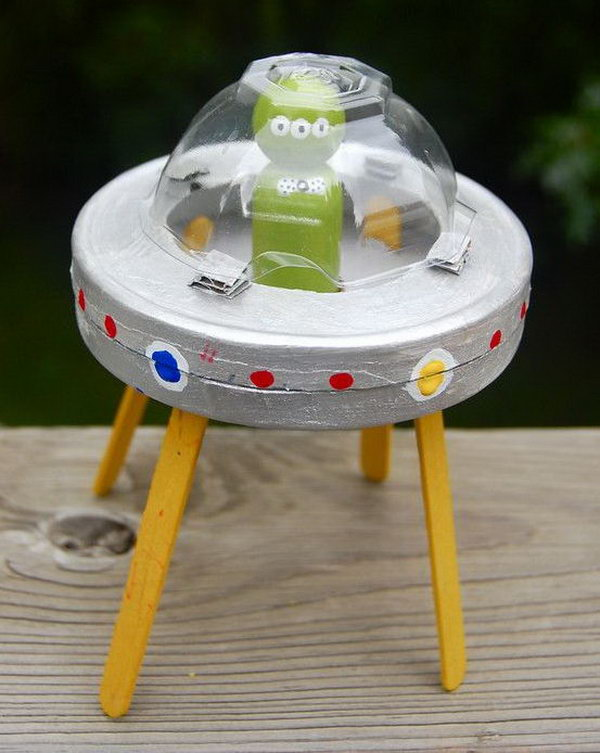 Use circular cream cheese box and popsicle sticks to create this alien and cardboard spaceship craft.