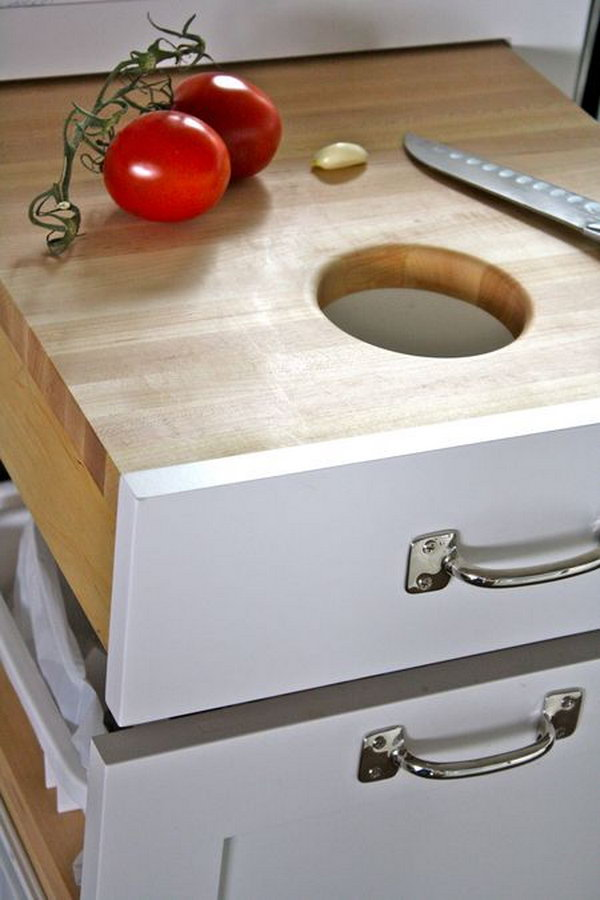 Put the cutting board in a drawer just over the trash can, so you can just scrape the unwanted scraps right in.