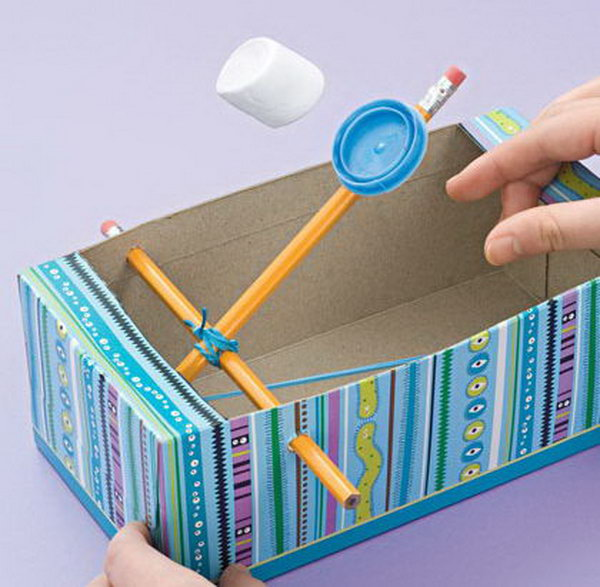 A Marshmallow Catapult for kids made from 2 pencils, a rubber band, a shoe box, and a milk cap. These would be fun and safe to create during force and motion lessons.