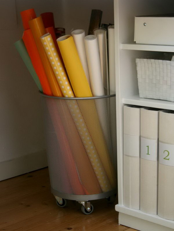 Add wheels to the bottom of a trash can for storing rolls of gift wrap. It feels super sturdy.