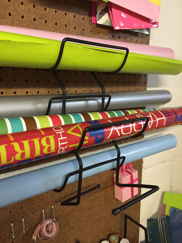Place these wine racks on the pegboard to hold rolls of gift wrap.