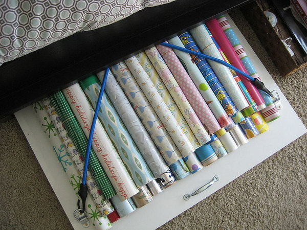Organize your wrapping paper under bed with a board with bungee cords.