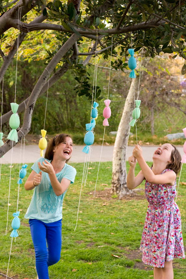 DIY Egg Popper Tree. Wrap the candy filled poppers like little egg shaped candies. Hang these up on a tree and let the kids pull and pop, gathering candy as they go. This is a cool and fun Easter egg hunt idea.
