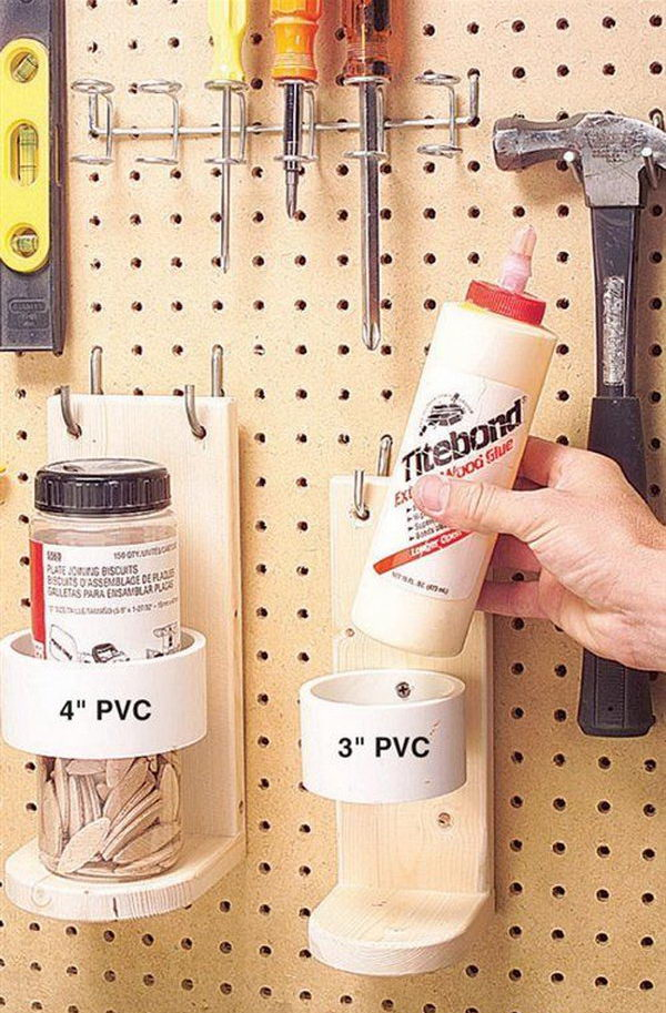 PVC pipe and wood bracket mounted to pegboard for garage storage.