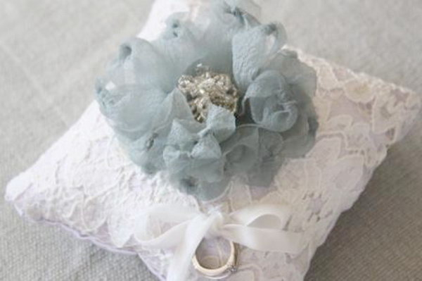 Fabric Flower Ring Pillow: Add the feather and fabric flower embellishments to the hand sewn pillow cover. This stunning DIY flower ring pillow would be perfect for your wedding decoration. See the tutorial