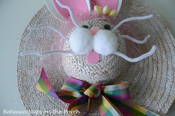 Bunny Easter Hat Decoration. Glue the ears from the form sheet of white and pink. Make the whiskers using pipe cleaners, stick the mouth and apply 3 pom poms above the whiskers. Finish it off with the colorful ribbon bow. This can be used to decorate the door too.