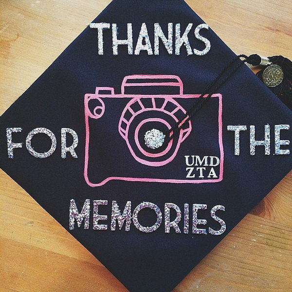 Painted Camera Graduation Cap. Stay in trend with this graduation cap painted with silver glittering wording as well as pink camera design.