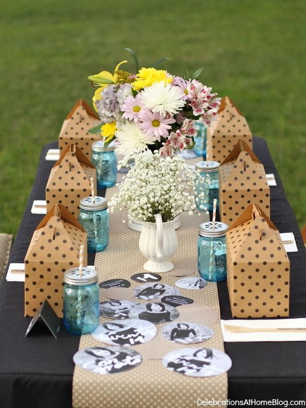 Elegant Graduation Table Decor. Use a chic, black tablecloth filled with flowers, mason jars, gift boxes and painted yearbook with personalized photos of the graduate to create an elegant table decor style to impress every guests come for your great celebration.