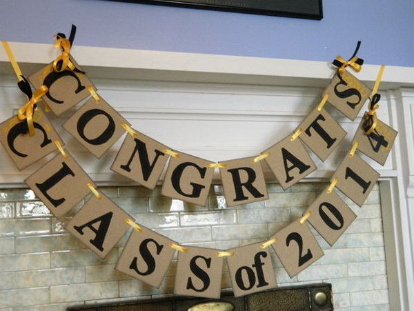 Graduation Banner Decoration. This handmade banner uses sunflower yellow acrylic paint for the swirl accents and ribbons bows of the same color to coordinate with the theme of the party to create a unique and vintage style.