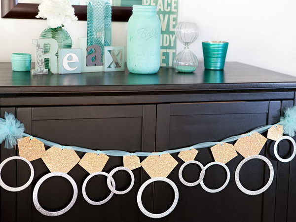 Glittering Ring Banner. This gorgeous diamond ring banner is perfect for a graduation party with its sweet outlook. Attach each circle to the diamond using adhesive scrapbooking. Insert the ribbon or tulle through eyelet hole to hang and celebrate.