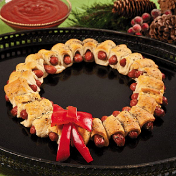 Mini Sausage Wreaths. Cutting prepared pizza into 32 pieces, wrap one strip of dough around mini sausage. Bake until the color turns gold. Add rosemary topped butter on top of the srescent wrappend sausages. Display in a wreath shape and add the bow made of red pepper for decoration to celebrate your Christmas party.