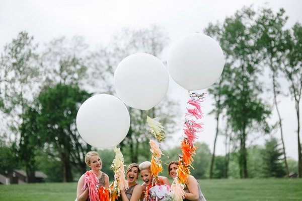 Giant Balloon Decor. Balloons are seen everywhere as decorations in various parties. Garnish your outdoor wedding with these giant balloons and add bright colorful paper tassels to the strings for your festive wedding event.