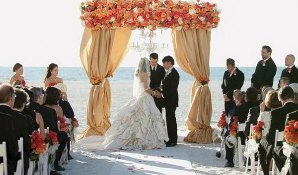 Floral Wedding Canopy. This enchanting canopy is super chic for a sand beach wedding with flowers limited to the top of your canopy for a romantic setup.