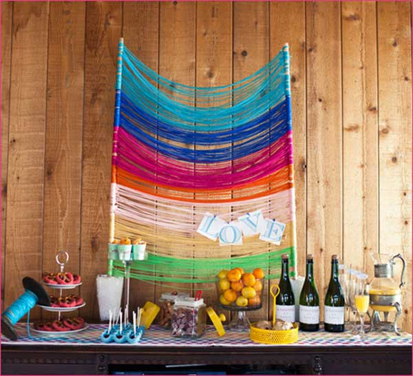 Colorful Yarn Backdrop. This glamorous backdrop decor will make a perfect starting point for your wedding ceremony. The yarn strung across your sweet table with the love word tied into it creates a sweet festive flavor.