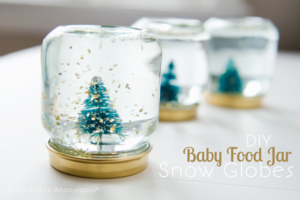 Baby Food Jar Snow Globes. Paint the lids gold, glue trees on the lid. Add gold glittering confetti, fill the jar with distilled water and Glycerin. You'll finish off the stunning mini snow globe for beautiful decor.
