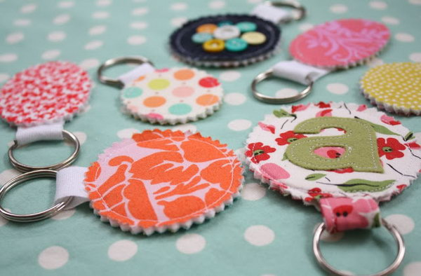 Fabric Scrp Keychains. Cover the pressing cloth with a beautiful applique, sew together and trim the edges, insert into your key chain and sew the opening closed to finish this elegant keychain in a cheap way.