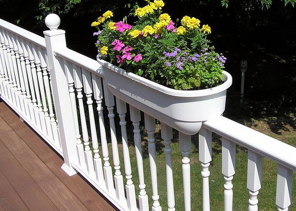 White traditional deck railing with planters. This white deck railing is really ornate but I especially love the planters. The flash of color of flowers give a beautiful look that adds the beauty of your railing.