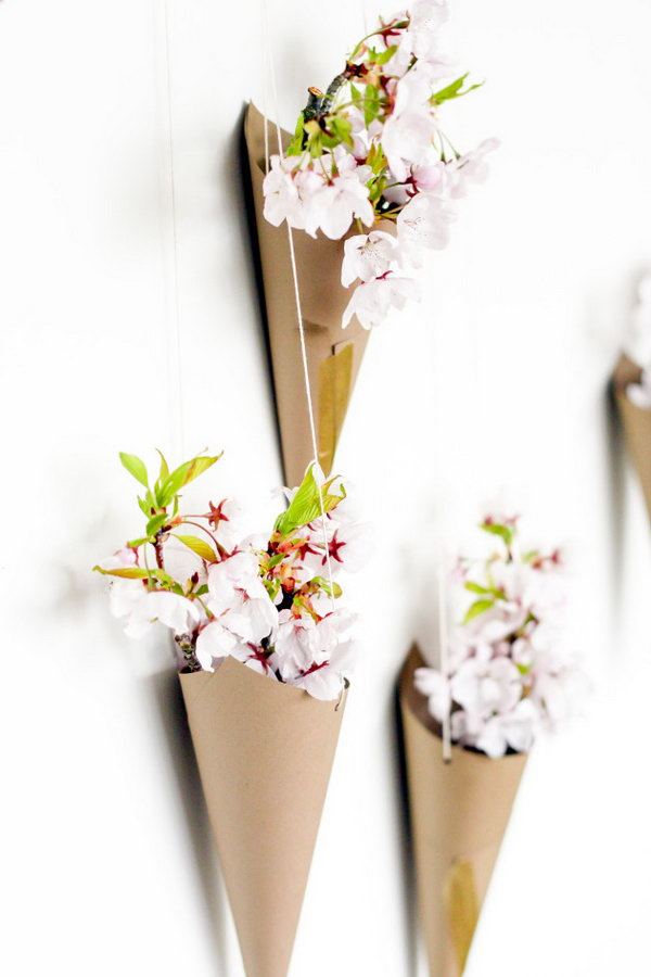 Blossoming Flower Cone Wall Display. Create cones from cardstock, punch 2 holes at both sides, take the string to hang the cone pointed side down. Arrange the cones on the wall and place some flowers in them to create the beautiful wall art for your dorm room.