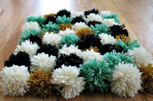 DIY Pom Pom Rug. Choose a color of yarn and wrap it around, tie a strand around the middle and cut the ends to make the pom pom. Create the rug using pom poms as you like. Arrange pieces of yarn in a grid, tie each pom pom to turn out your design to add color, texture and comfort to your dorm room.
