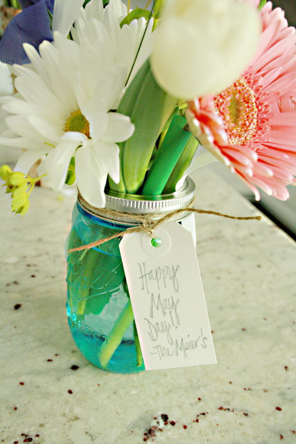 Flower Jar for May. Grab some ribbon, twine a little tag. Fill your mason jars with water, make a beautiful arrangement of flowers to your imagination. Place the screw band on the jar. You'll get this artistic flower jar for May in beautiful design.