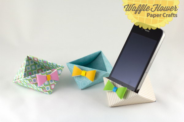 iPhone Paper Triangle Stand. Score and fold each square patterned paper, tuck each corner next to the other to create the container. Tie the bow for beautiful garnishment to finish off your paper stand in this elegant way.