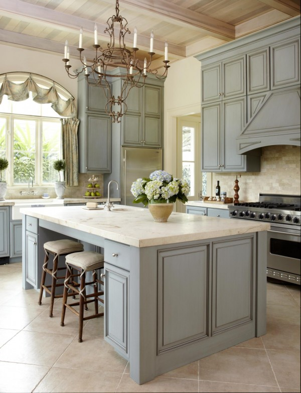 Pastel Colored Kitchen. The colours are warm and so comfort and restful. This kitchen island is accented with beautiful classic green cabinets and lighting fixtures.