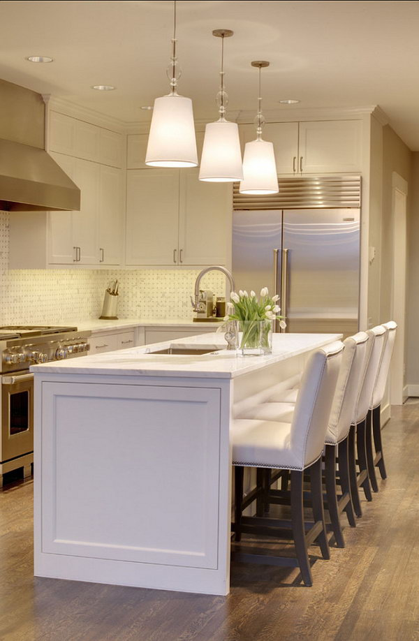A Bright Spot.An all in white island with simple lines, echoes this kitchen's white pendants and white elegant custom made chairs. Stainless steel appliances add to very stylish and morden look.