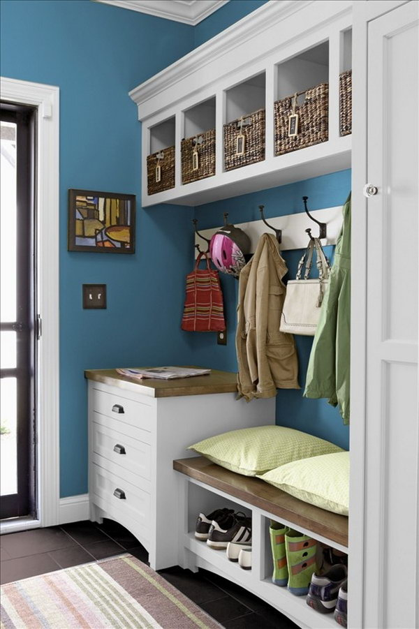 White and blue mud room.  This little mudroom is beutifully made with white and blue color palette, basket storage, big hooks to hang up coats, easy to clean black flooring, bench.