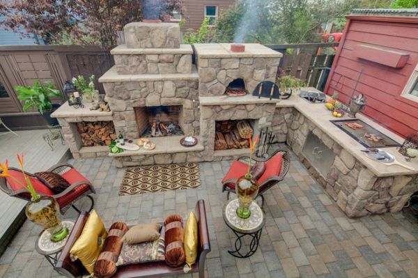 This outdoor kitchen is fully equipped with everything necessary for cooking, a simple pizza oven, fireplace and many other cool cooking tools.