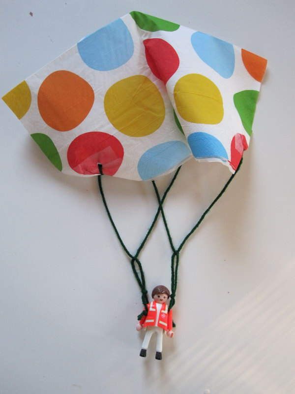 Toy Parachute Craft. Use clear tape to reinforce your napkin and punch holes for the yarn to tie through. Tie two stands and make two more knots together, then you can pop them and drop. It's so funny and you can play inside without going outside on hot summer days.