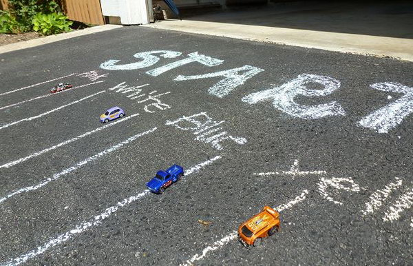 Racetrack on the Driveway. Use tape or chalk to draw lanes down the driveway. You can also make a race ramp out of wrapping paper tubes to give the cars some acceleration. This game is especially designed for boys to play in summer.