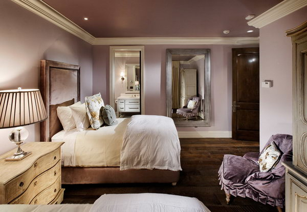 Mirror on the wall: In this bedroom, the dark, rustic flooring and door contrasts with the lighter tones of the contemporary bed and chair. Painting the ceiling the same color creates a cozy and intimate space, keeping the moldings white helps brighten the space. Loving the mirrors on the wall which keep the space from dark.