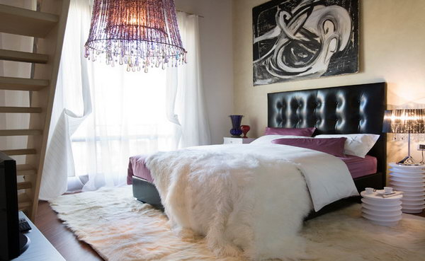 Touches of Purple: This bedroom with a striking chandelier and a leather headboard and the impressive modern wall art really looks rock. Yet the faux animal furs and the touches of purple on the bedding infuse warm and soft. Good example of interpreting purple in different textures
