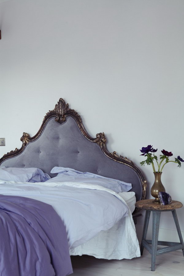 Eye Catching French Headboard: In the master bedroom, a French headboard is reupholstered in a soothing purple gray velvet that blends well with Farrow & Ball Great White painted walls.