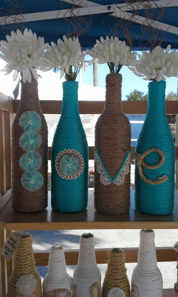Upcycled Rope wrapped Wine Bottles as a wedding Decor. These adorable rope wrapped wine bottles with the letters to spell LOVE are wonderful for a wedding with flowers in.