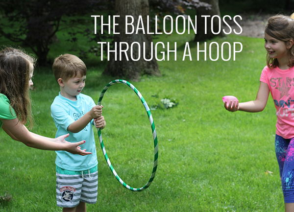 Balloon Toss through a Hoop. Ask one kid to hold the hula hoop and the other kid try to toss the water balloon through the hoop. It's challenging yet interesting.