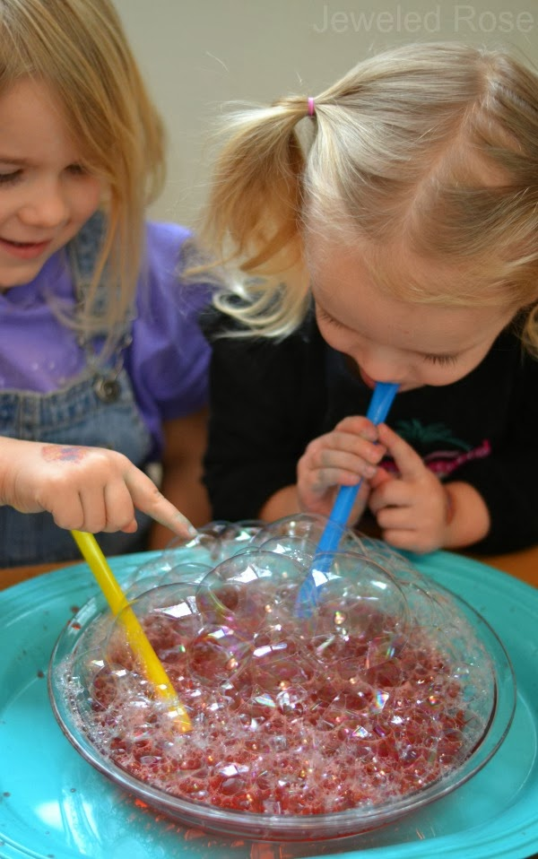 Play with bubbles. Children love to play with colorful bubbles and they would never be bored with this game. All you need is one or two containers, water, dish soap (I used Dawn) and a straw.