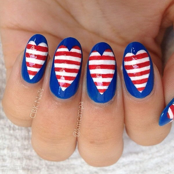 4th of July Love Nail Art: This design is a funky take on flag inspired nails. Start with a navy blue base and heart middle. Then freehand paint the white and red stripes using a nail art brush. I love the American heart so much.