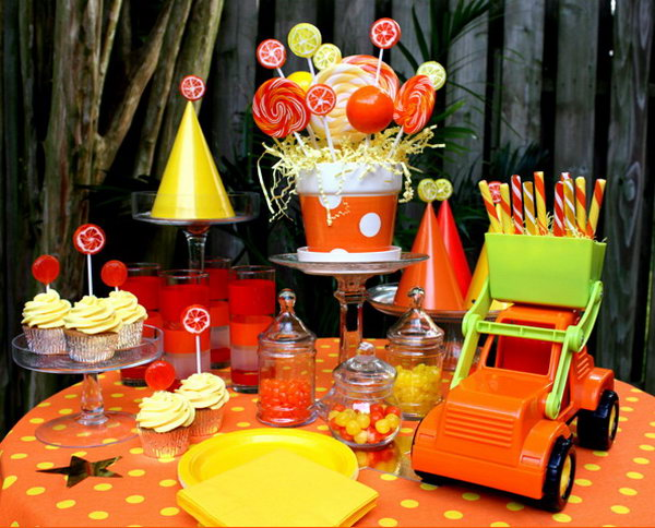 Truck Birthday Decoration: The Dump Truck served as a great decoration and the lollipop bouquet in a bright planter are great. Love the smaller lollipops as cupcake toppers, and glued leftover lollipops to the top of the party hats for some extra pizzazz! Glass cake stands and apothecary jars helped display all the different goodies.