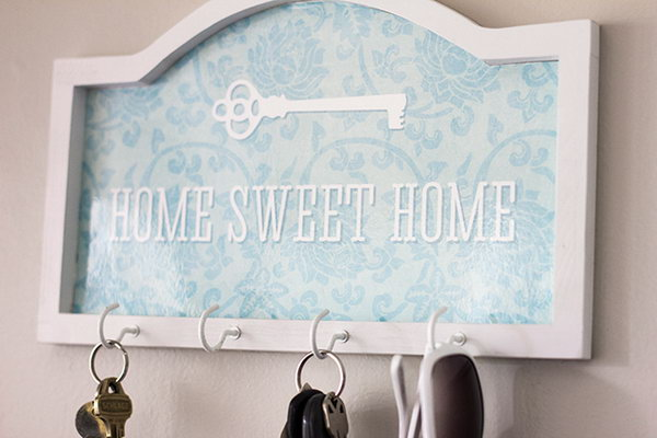 Sweet and Simple Key Holder. This piece for the wall is sweet and easy to make. The component elements are simple: a shaped piece of wood, hooks and for the aesthetic part are some patterned wrap paper. The finished product looks wonderful with or without keys. See the tutorials