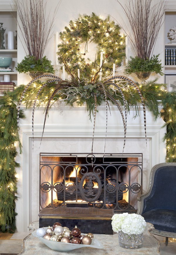 Hanging Green Christmas Wreath over White Wood Mantel with Green Leaves and Long Feathers on the Mantel