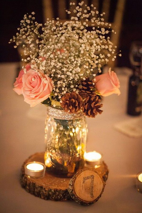 50 budget friendly rustic real wedding ideas hative stunning rustic mason jar centerpiece with pine cones candles and wooden table number junglespirit Choice Image