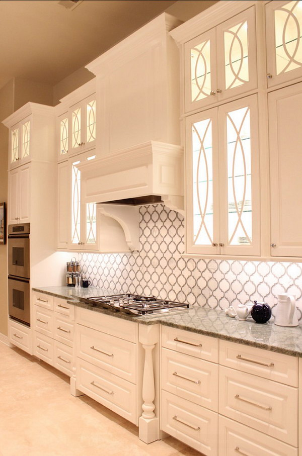 gold marble and grey glass backsplash with beautiful white cabinetry
