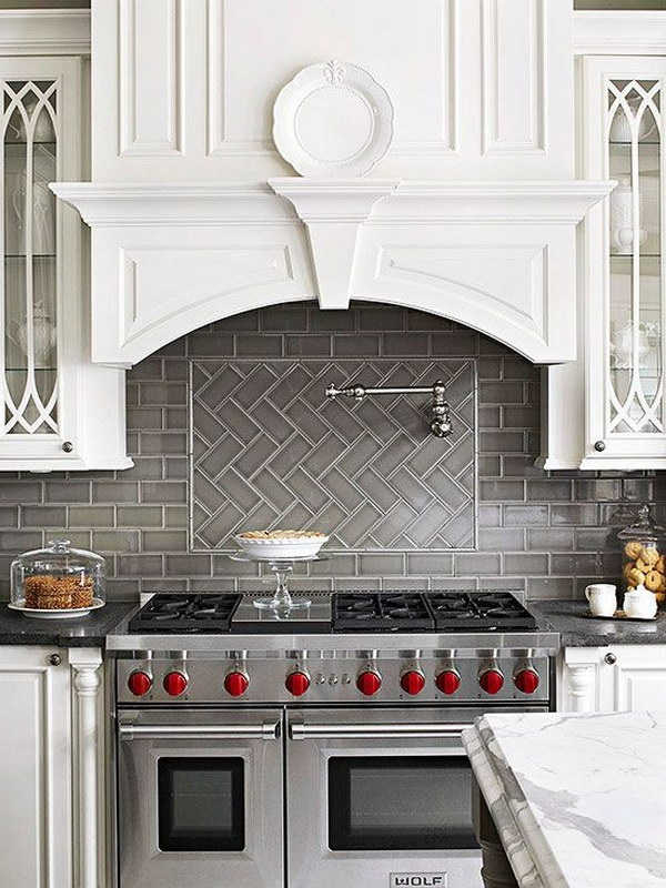 Grey Herringbone Subway Tile Backsplash Works with the Stainless Stove  against White Cabinetry