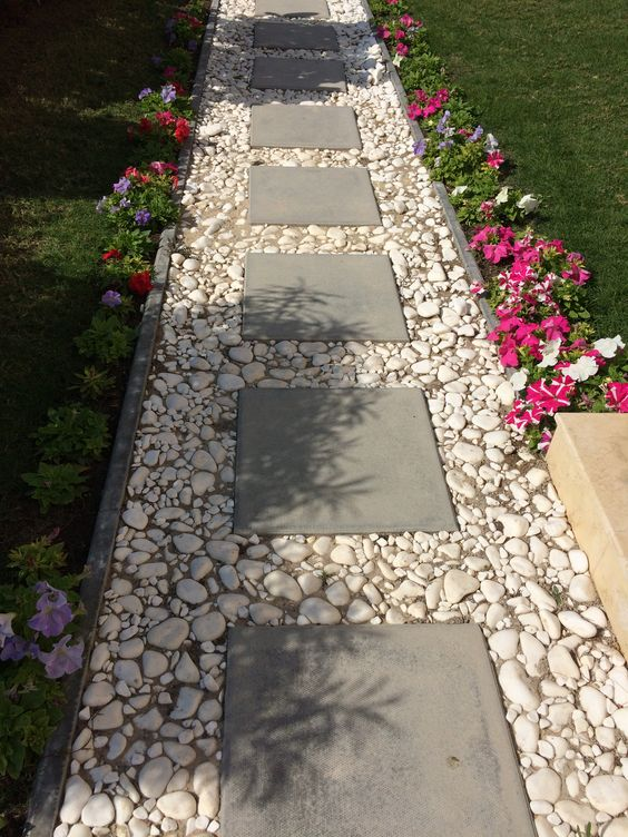 A Simple Pathway With Cement Block Tiles Bordered By White Pebbles