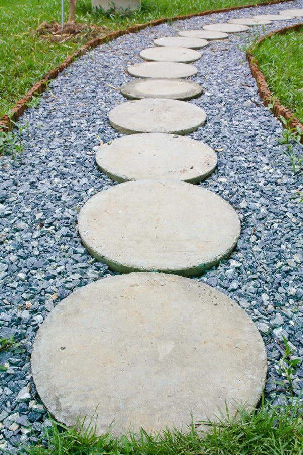 Circular Concrete Stepping Stones Laid On A Darker Gray Set Of Gravel for Pathway.