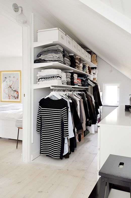 Build an Attic Closet Against the Attic Wall Using Shelves and Low Hanging Rod.