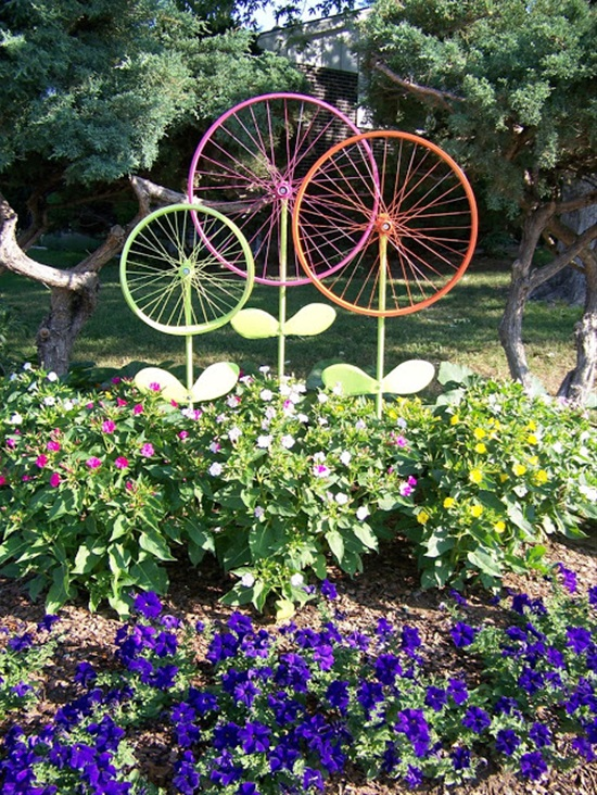 Old Bicycle Rims Painted Bright Colors Make Flowers in the Garden.